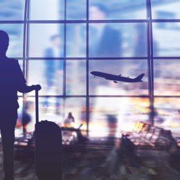 man in airport terminal watching an airplane take off at dusk