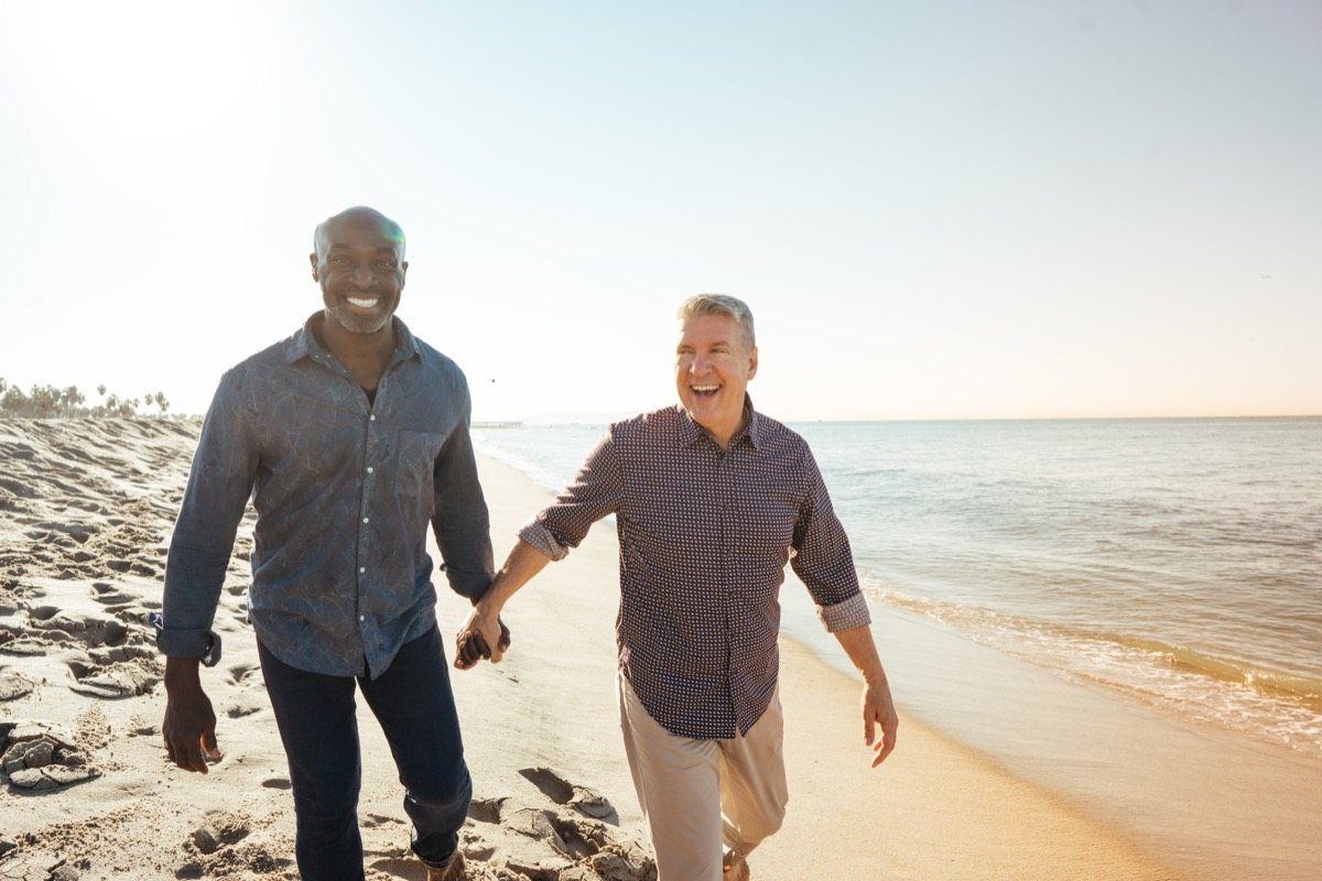 old couple walking on beach together