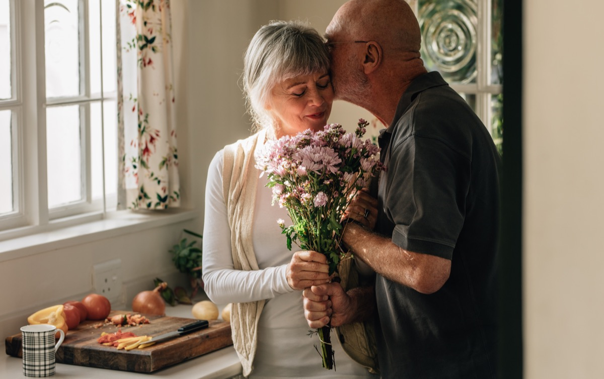 old man surprising his wife with flowers