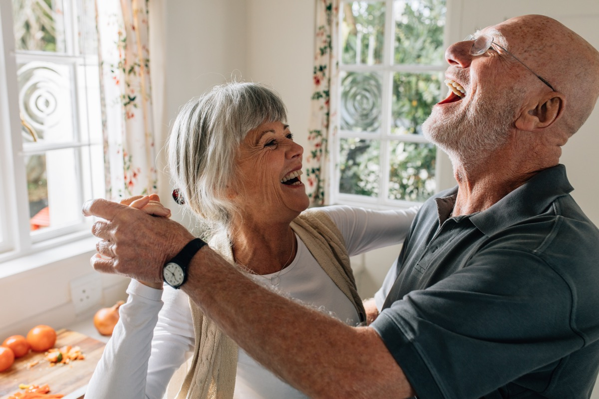 older couple dancing in their kitchen together