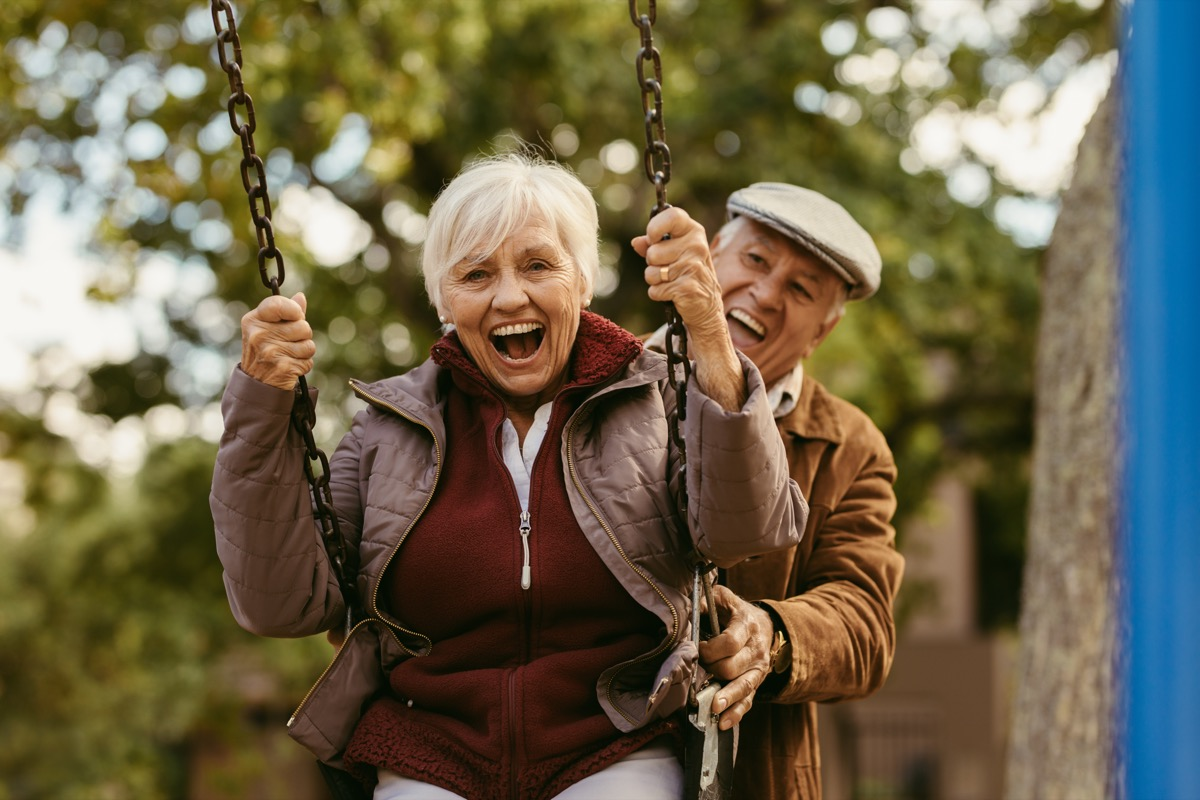 old man pushing his wife on a swing