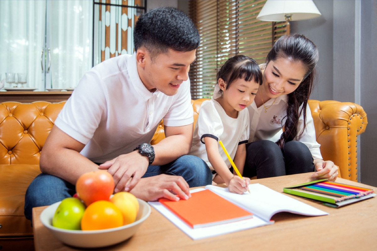 asian parents helping young child with homework being a step-parent