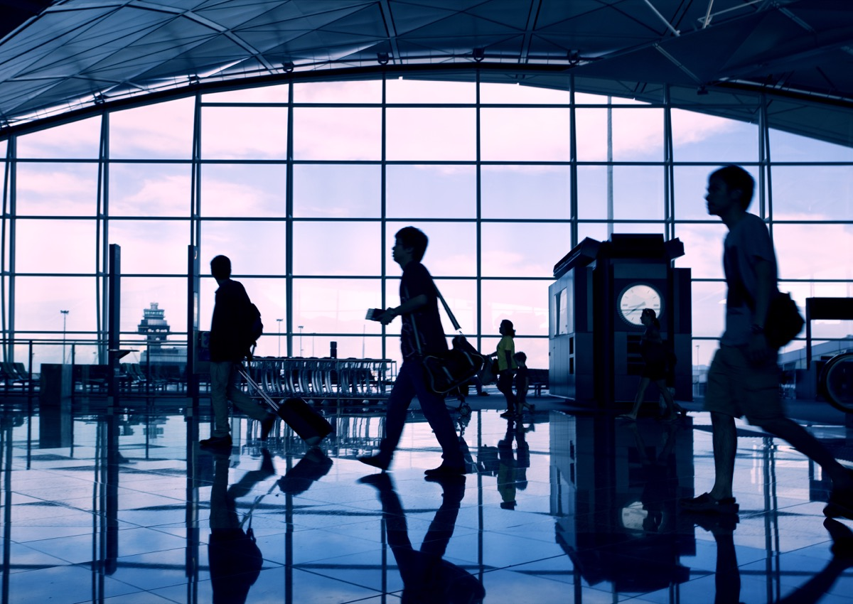 passengers walking in an airport terminal at dusk