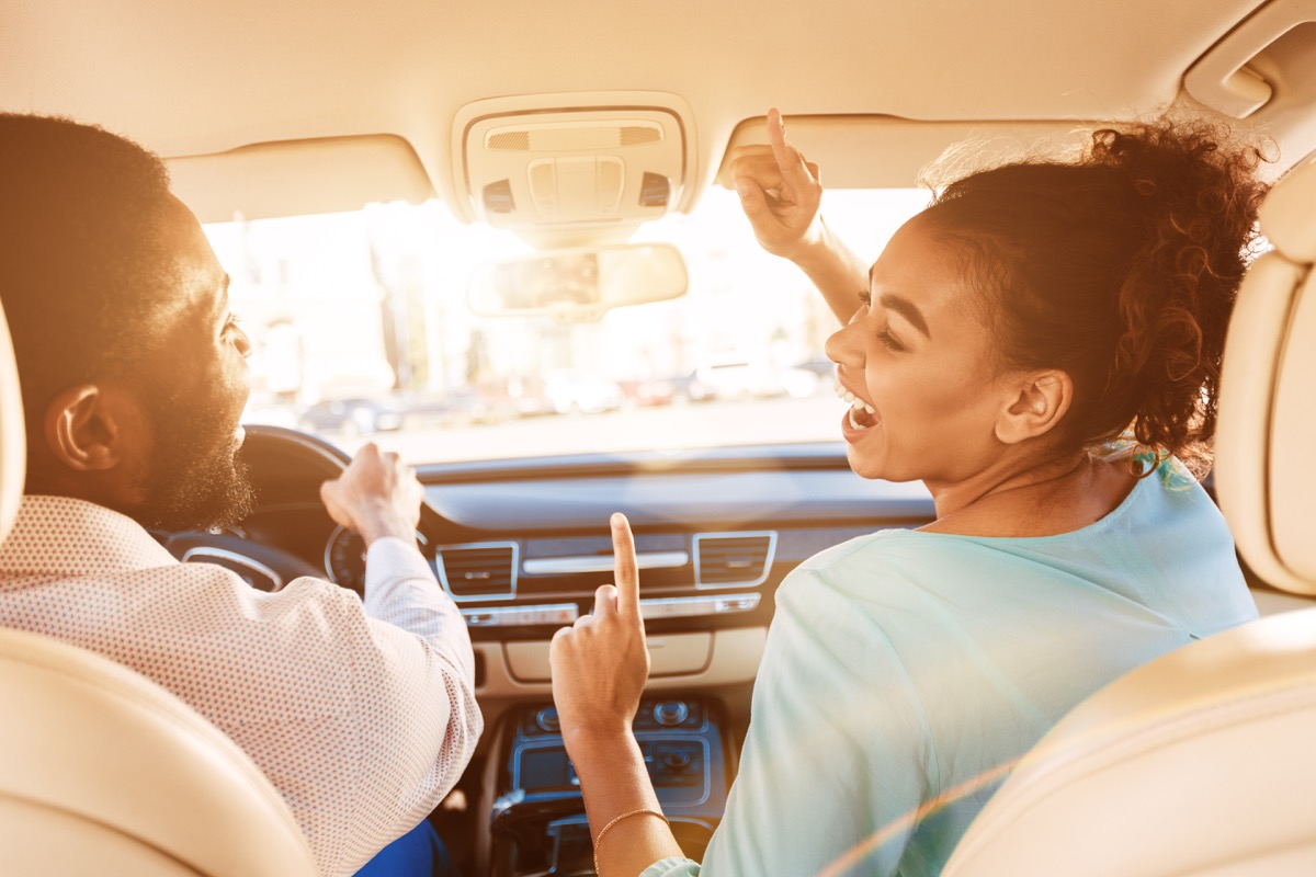 Young man and woman singing in car