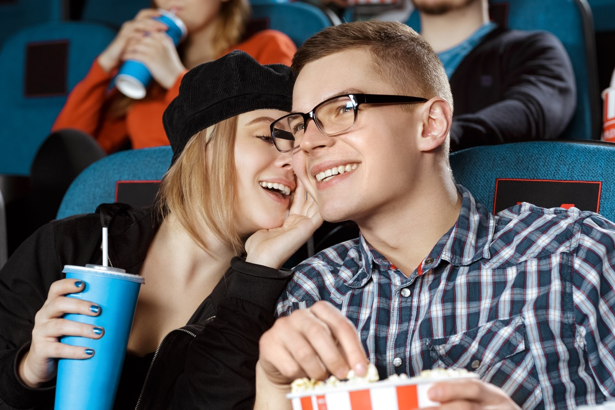 Couple whispering in a movie theater