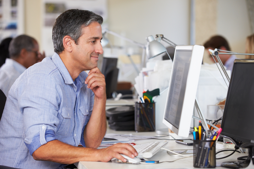 happy middle-aged man working in office procrastinate productively
