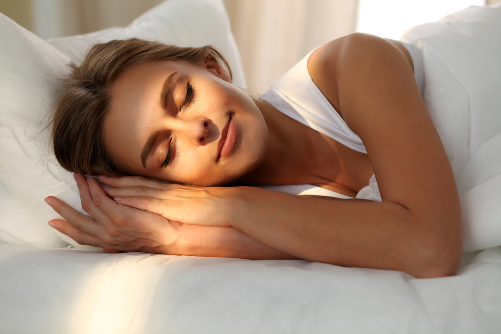 woman sleeping in bed with light shining on her