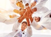 a bunch of doctors smiling and putting their hands together in a circle showing team spirit