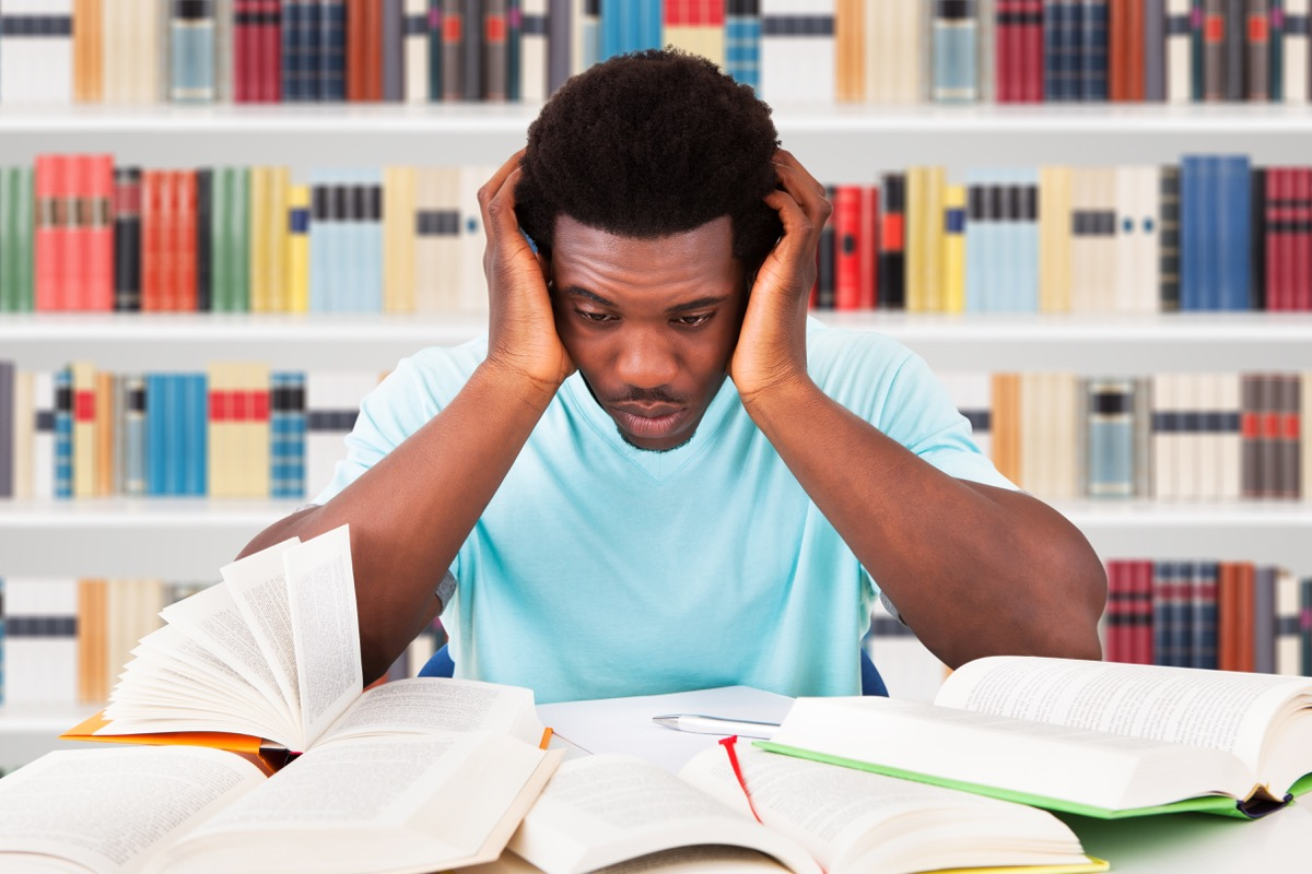 African American college student looking stressed in the library ways college is different