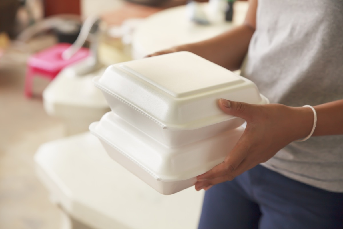 Woman holding styrofoam boxes