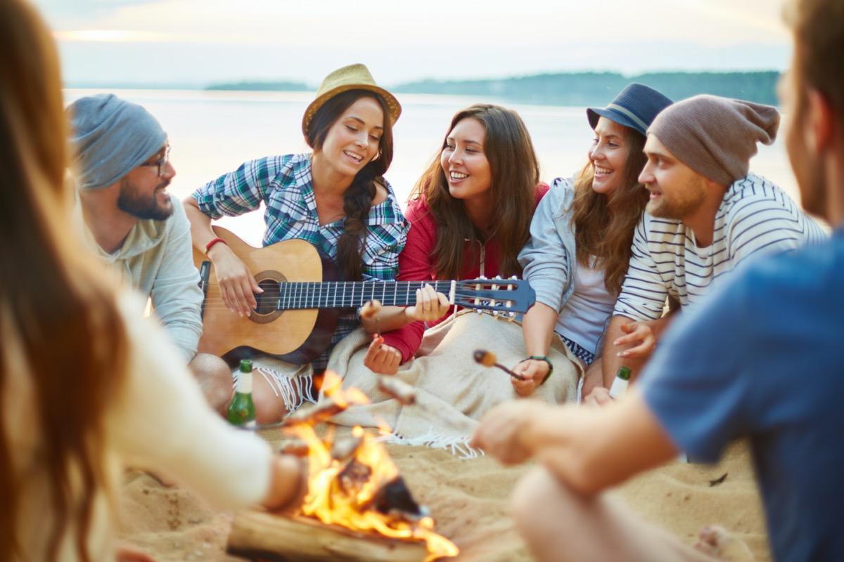 a group of men and women sing songs around a campfire