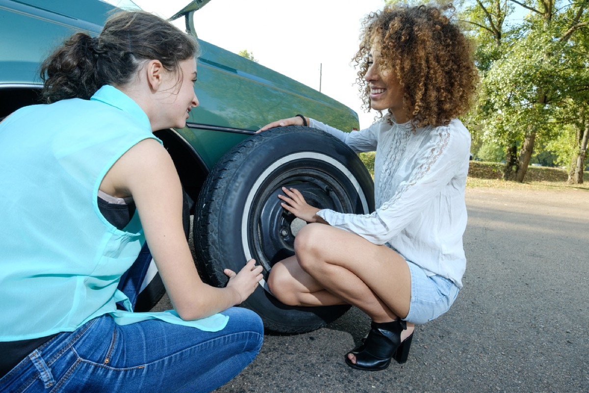woman teaching girl to change flat car tire, skills parents should teach kids