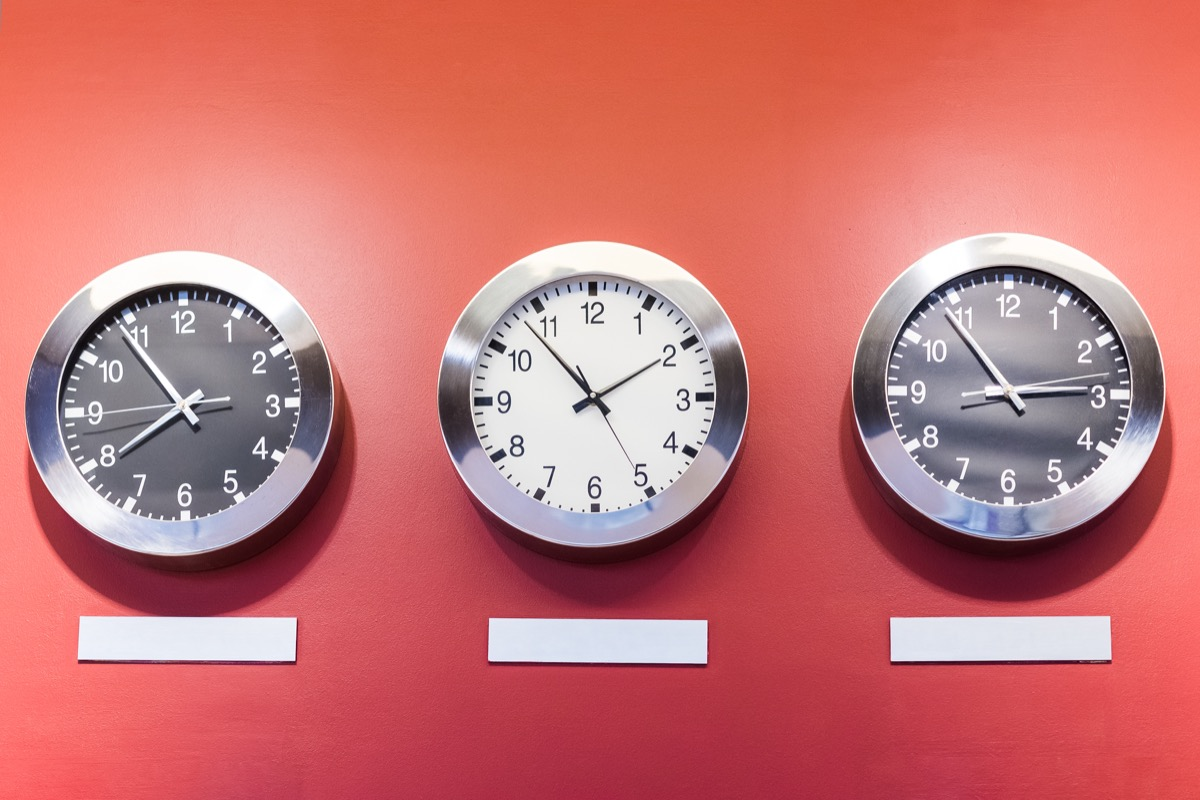 Three clocks on wall showing different time zones