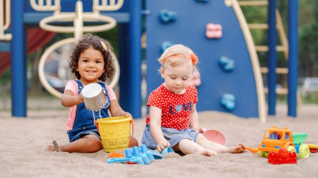 two toddlers playing in sand on playground, best outdoor toys for toddlers