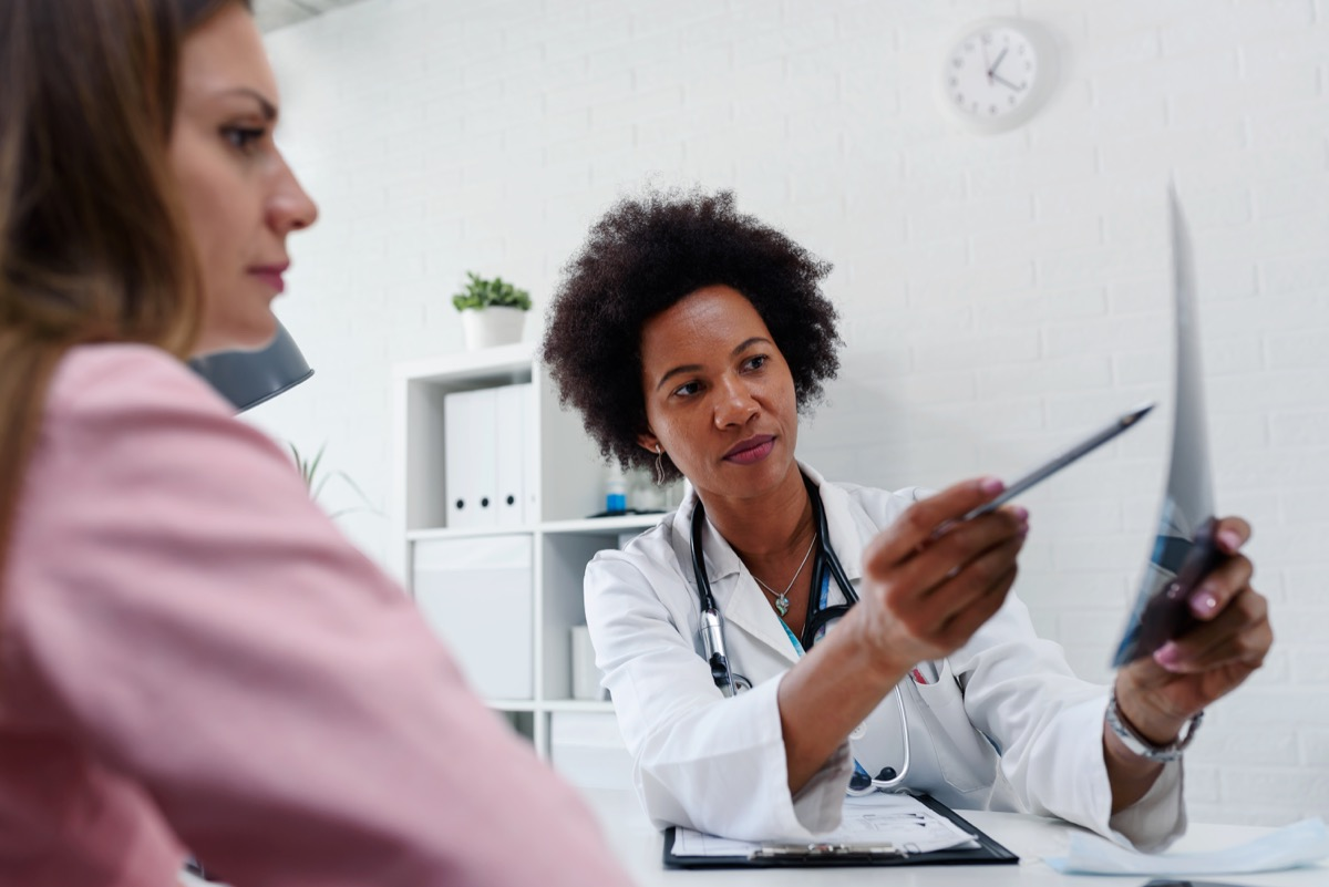 Doctor talking with patient at desk in medical office