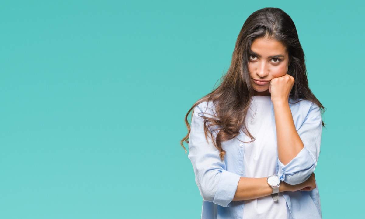 an annoyed woman against a teal background