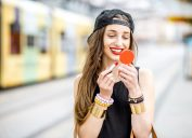 hipster woman applying red lipstick outdoors, summer beauty products