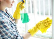 woman wiping window with cleaner, cleaning mistakes