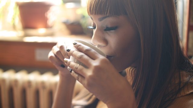 Black woman sipping on tea or coffee