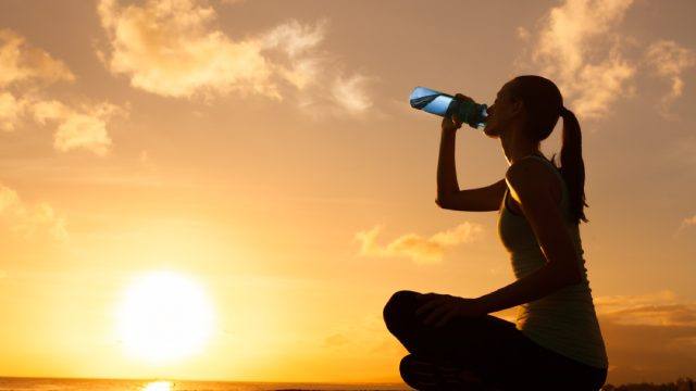 woman outdoors drinking water in front of sunset, cute water bottles