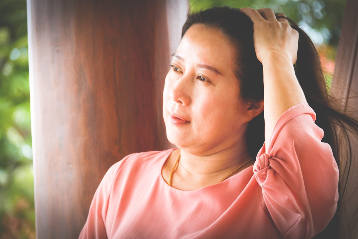 Asian Woman Pale in the Face From Feeling Sick Signs of Poor Health Over 50
