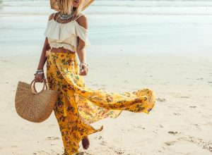 woman in yellow tote holding woven bag on the beach, luxury beach bags