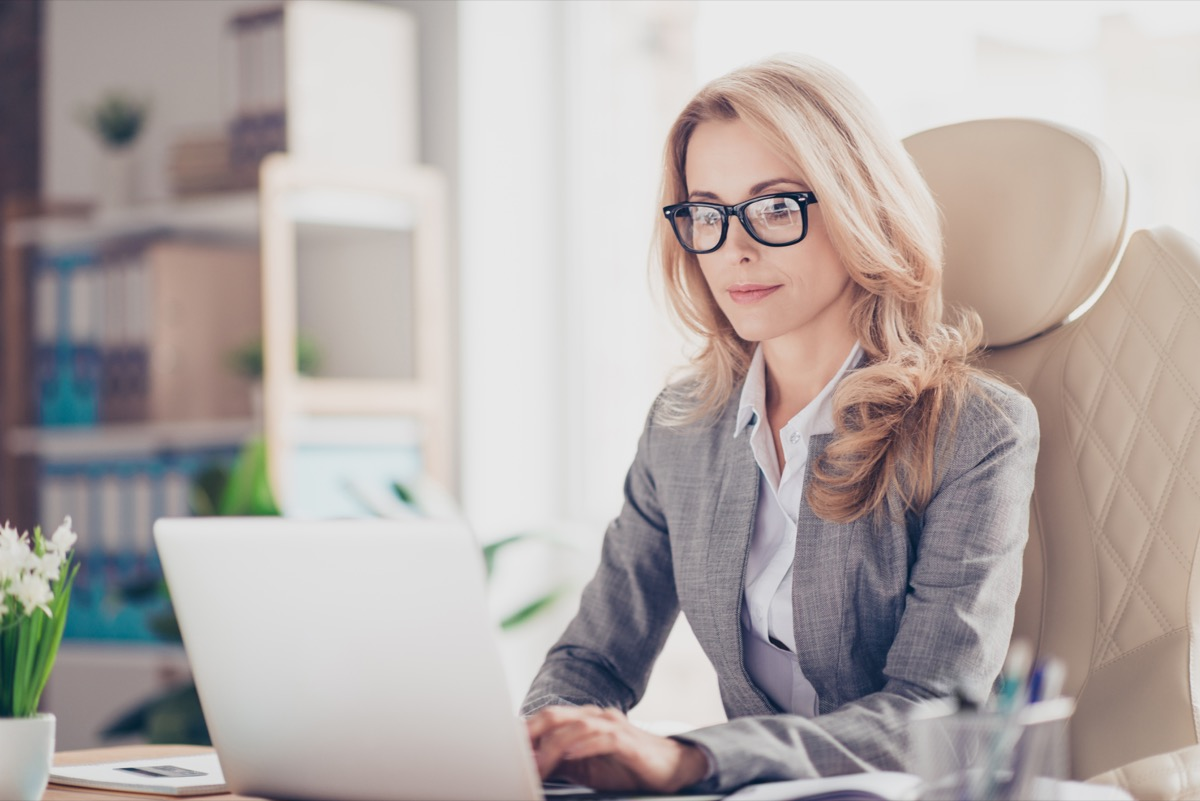 woman sitting at a desk in front of a laptop, ways to feel amazing