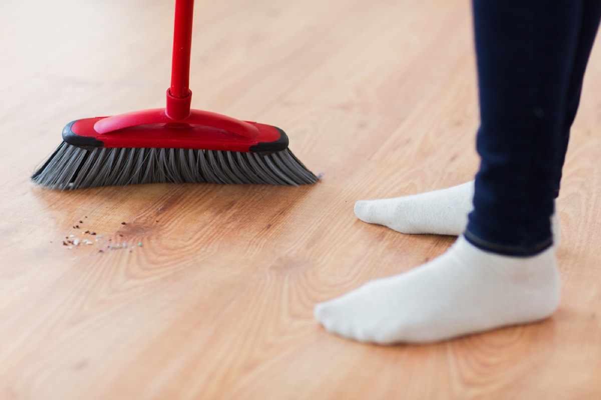 person using broom on hardwood floor, how often you should replace your cleaning supplies