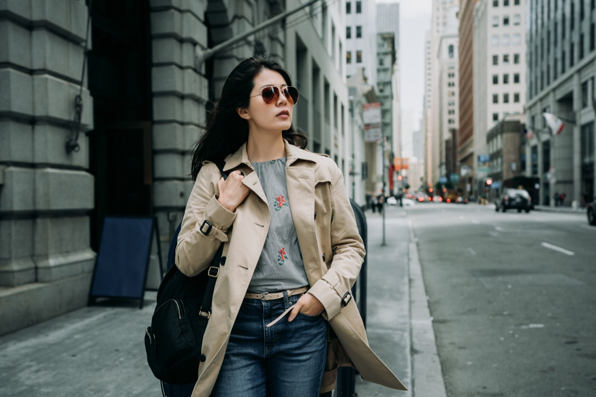 a woman wearing a tan trench coat and ray-ban sunglasses walking on a city street during a cloudy day