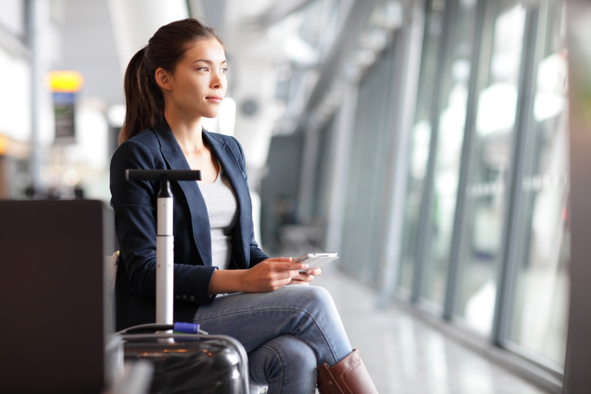 woman waiting in an airport sitting next to luggage while scrolling through a smartphone