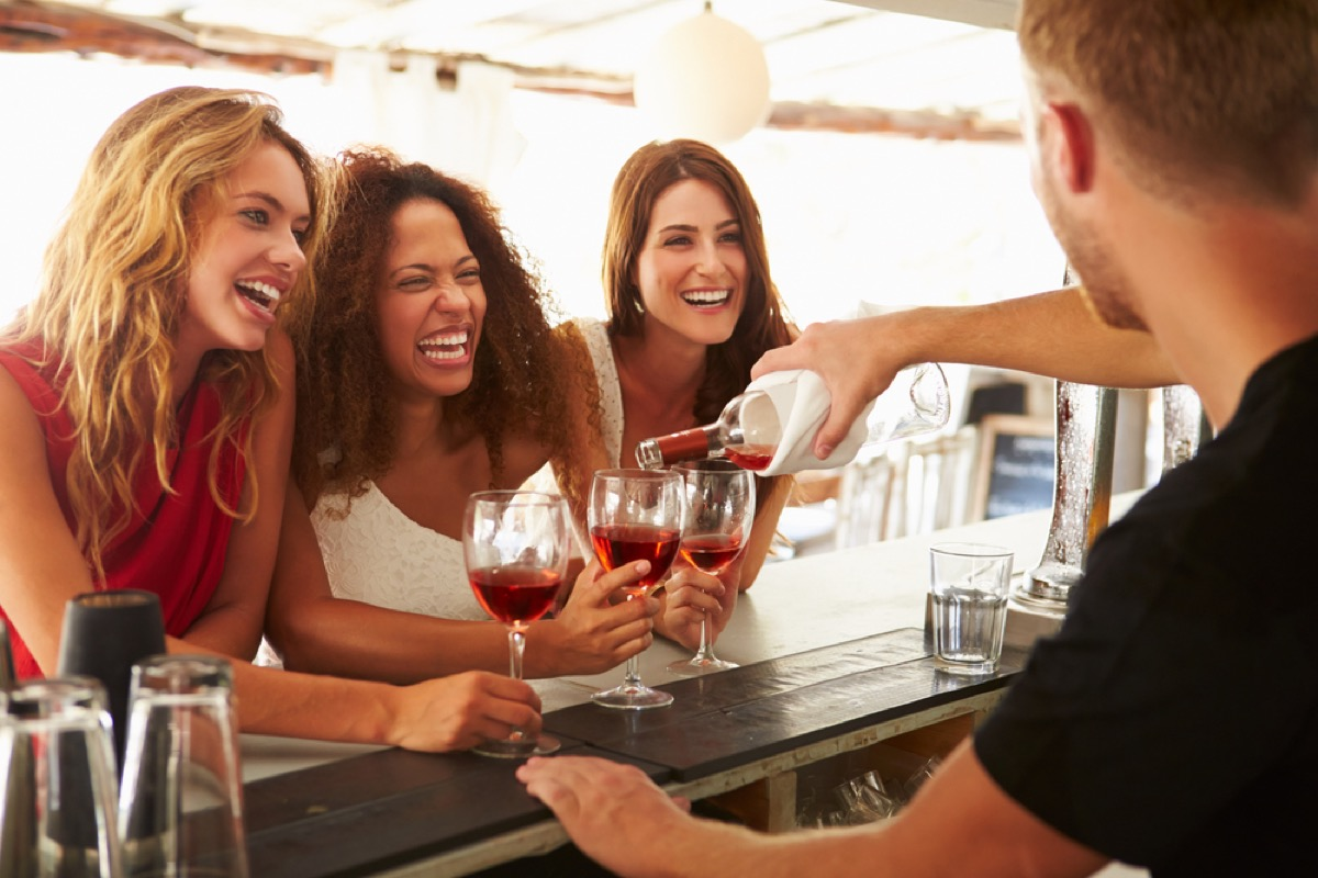 three women with glasses of wine laughing together, female friend
