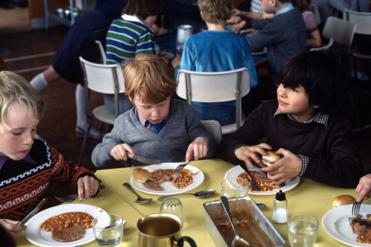 1970s historical image of school meals in primary education in the 1970's where instant food was served with very little fresh greens