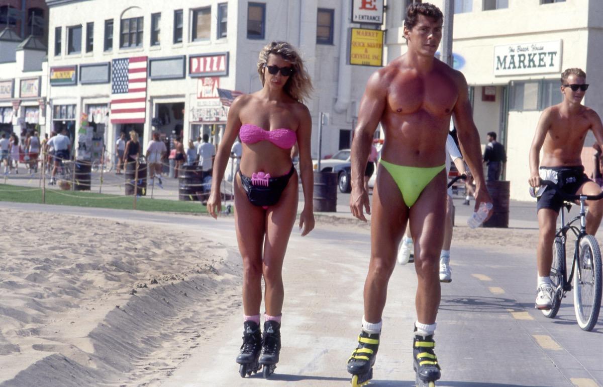 Couple rollerblading in neon in Venice Beach, California circa the 1980s.