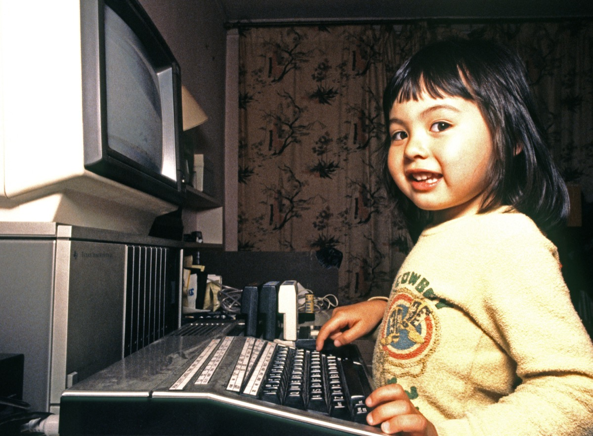 three year old Asian girl plays with a TI 99 4a home computer, 1986.
