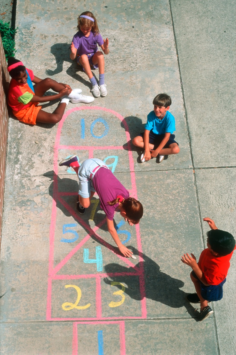 1980s GROUP OF FIVE CHILDREN BOYS AND GIRLS PLAYING HOPSCOTCH ON CONCRETE SIDEWALK