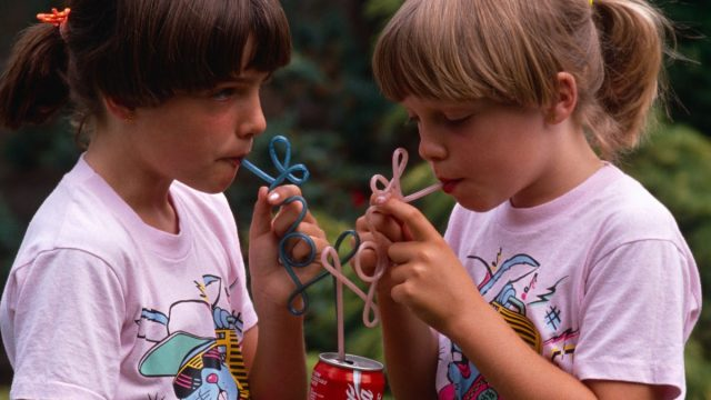 In 1980s, Two young twin sisters sip Coke from their own curly straws in an English garden, UK