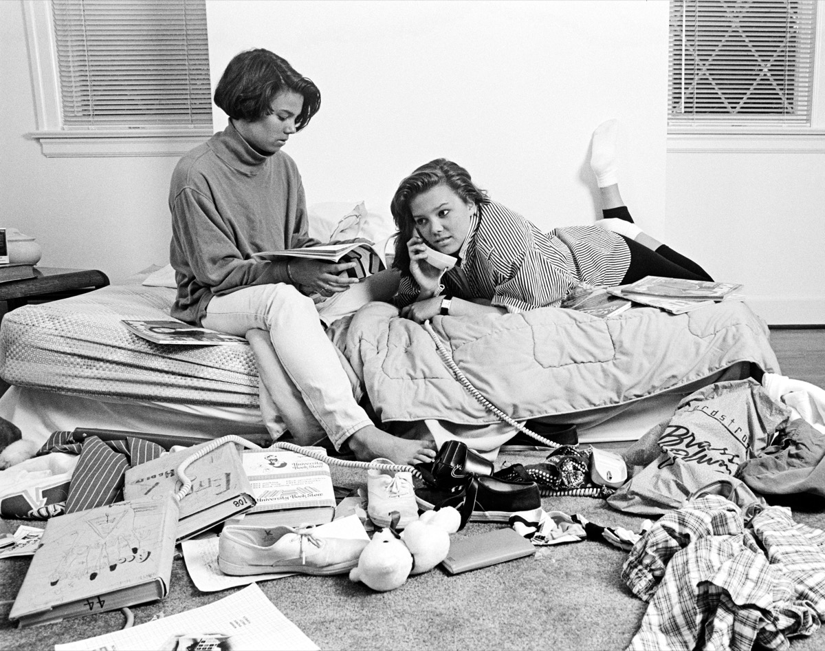 TWO TEENAGE AFRICAN AMERICAN GIRLS IN CLUTTERED BEDROOM ONE TALKING ON THE PHONE ONE READING MAGAZINE