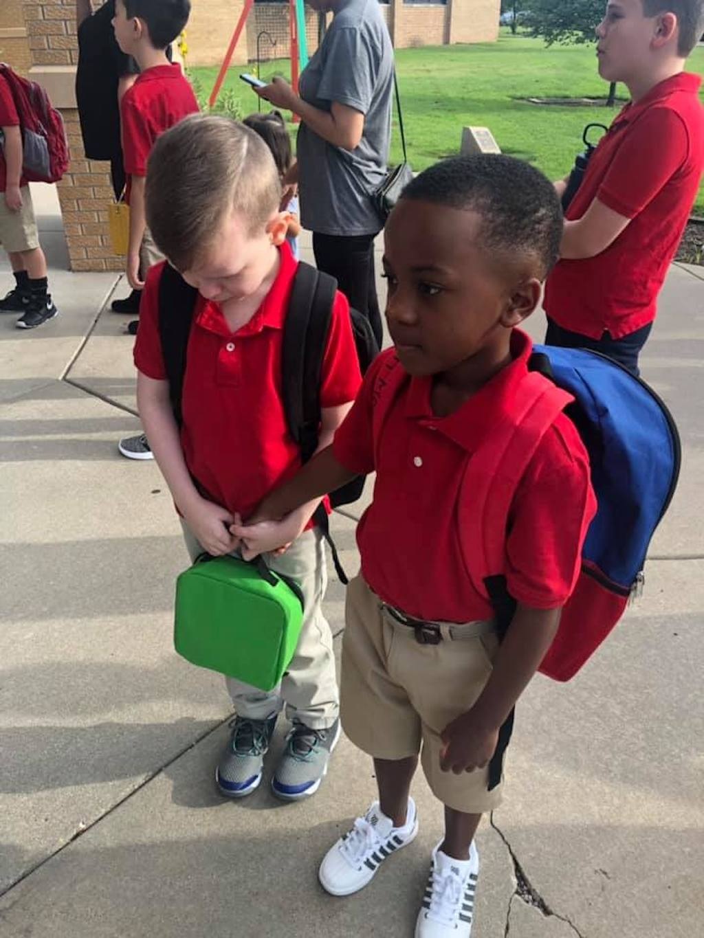 Christian holds hand of autistic boy Connor on the first day of school
