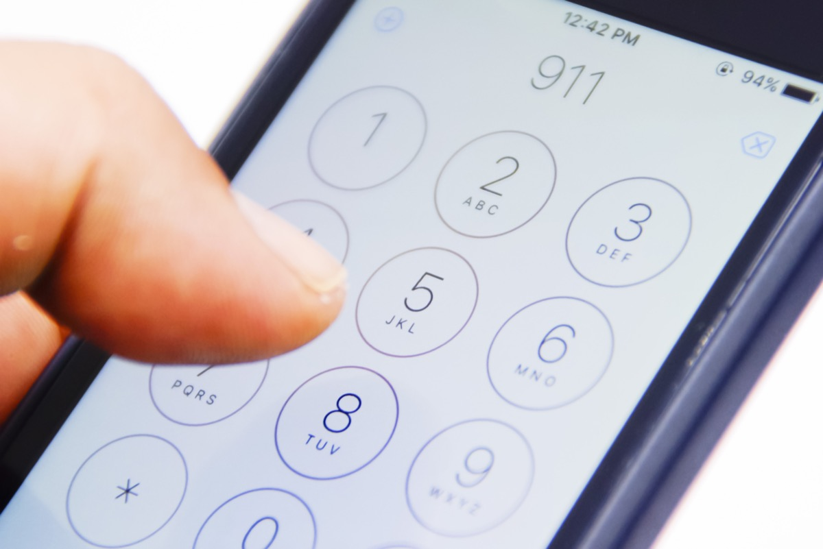 Finger dialing 911 on smartphone