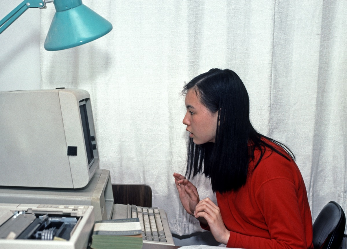Asian girl using a PC home computer in 1990s