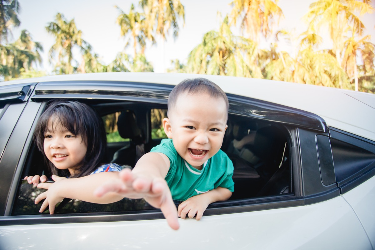 Asian kids laugh in backseat of car