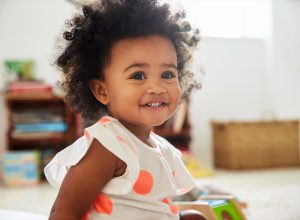 Happy Baby Toddler Playing With Toys In Playroom
