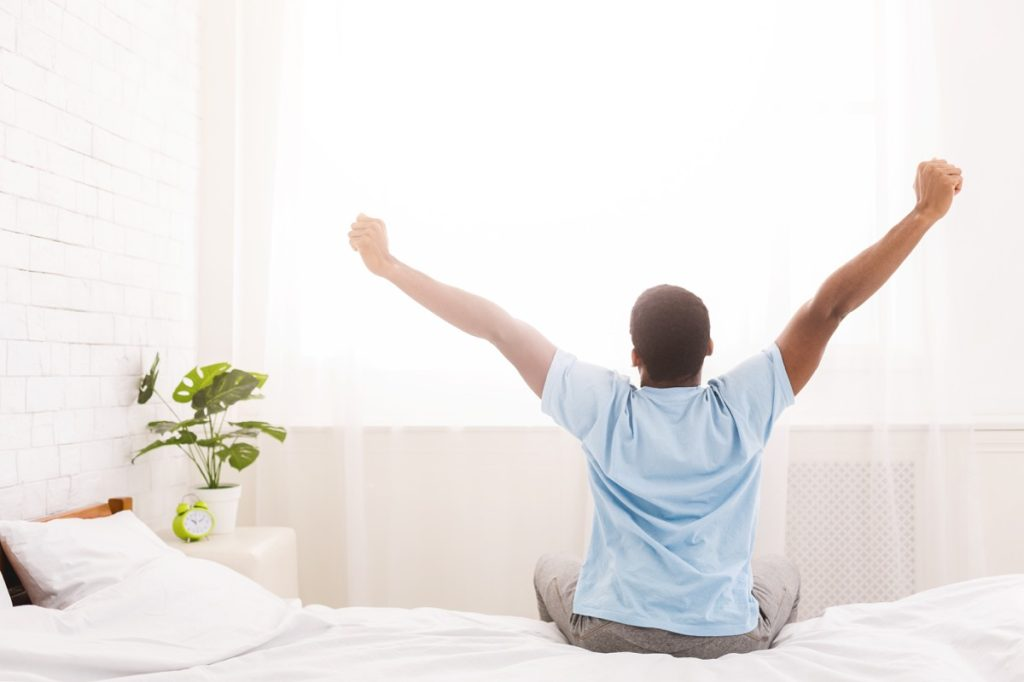 Black man pictured from behind stretching in bed in the morning, wearing a blue shirt, savory breakfast leads to success study