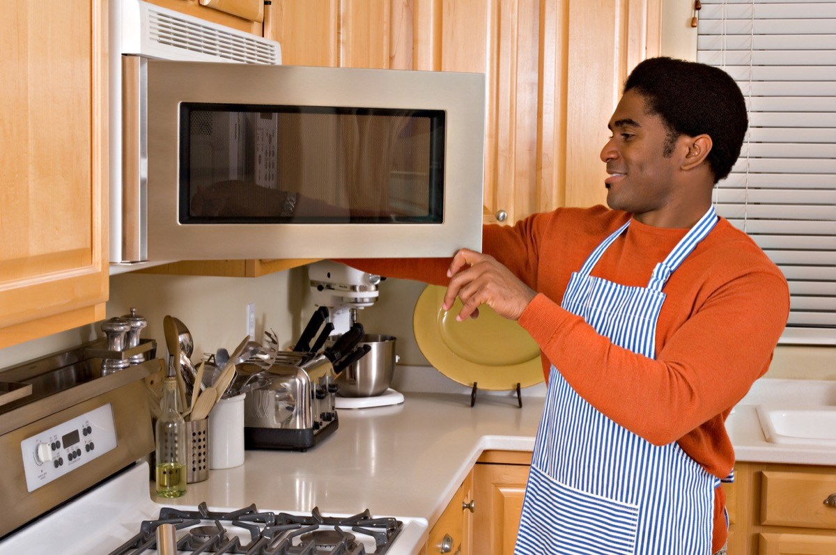 African-American man uses microwave to cook dinner in kitchen
