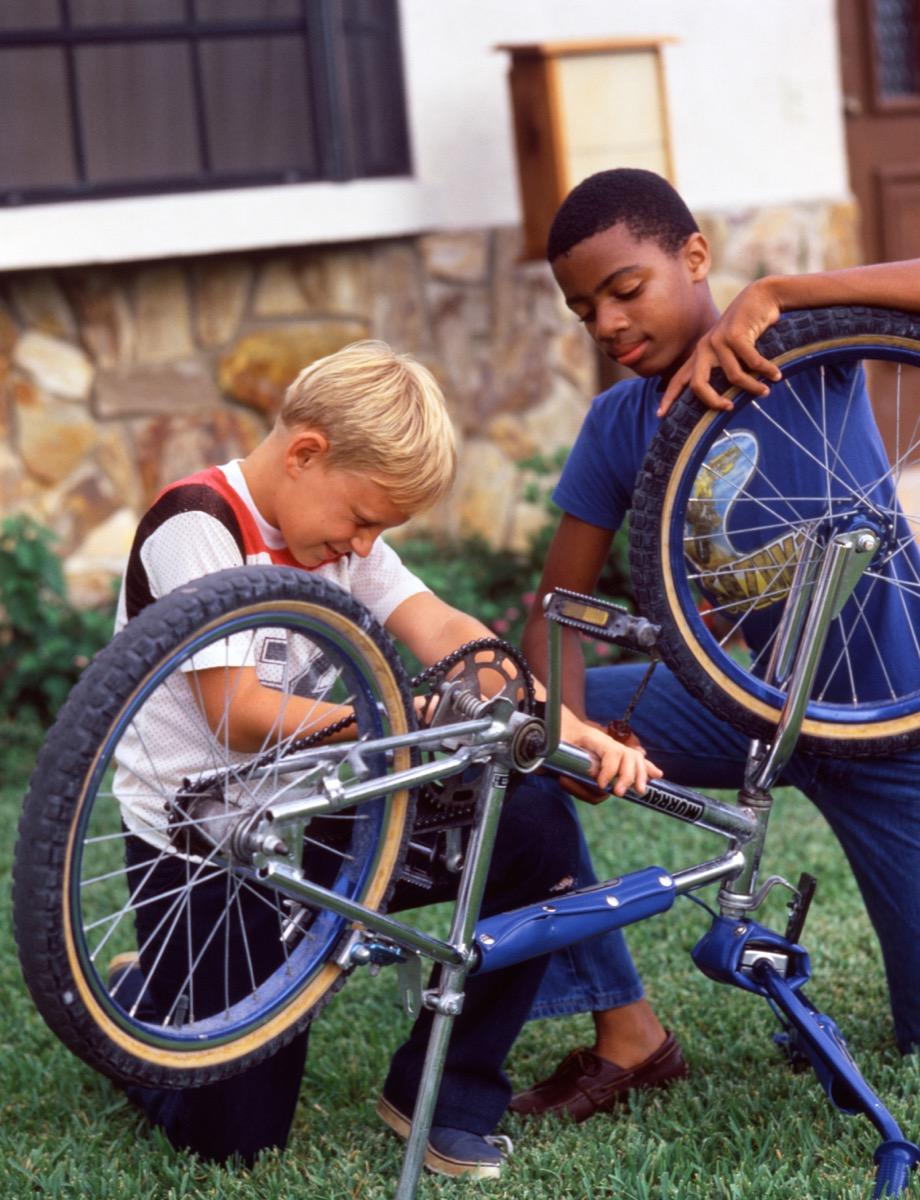 Black and white boy fix bike 1980s