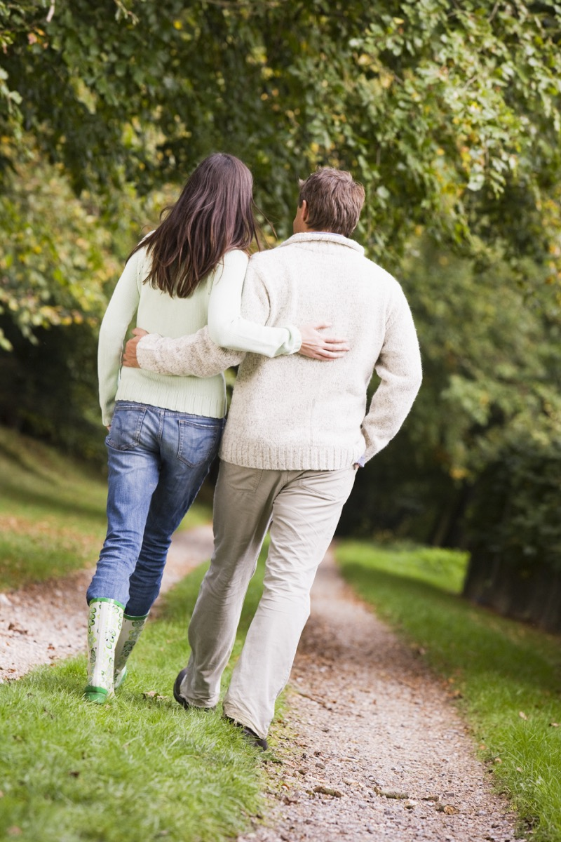 Couple walking in countryside from behind, widow at 40
