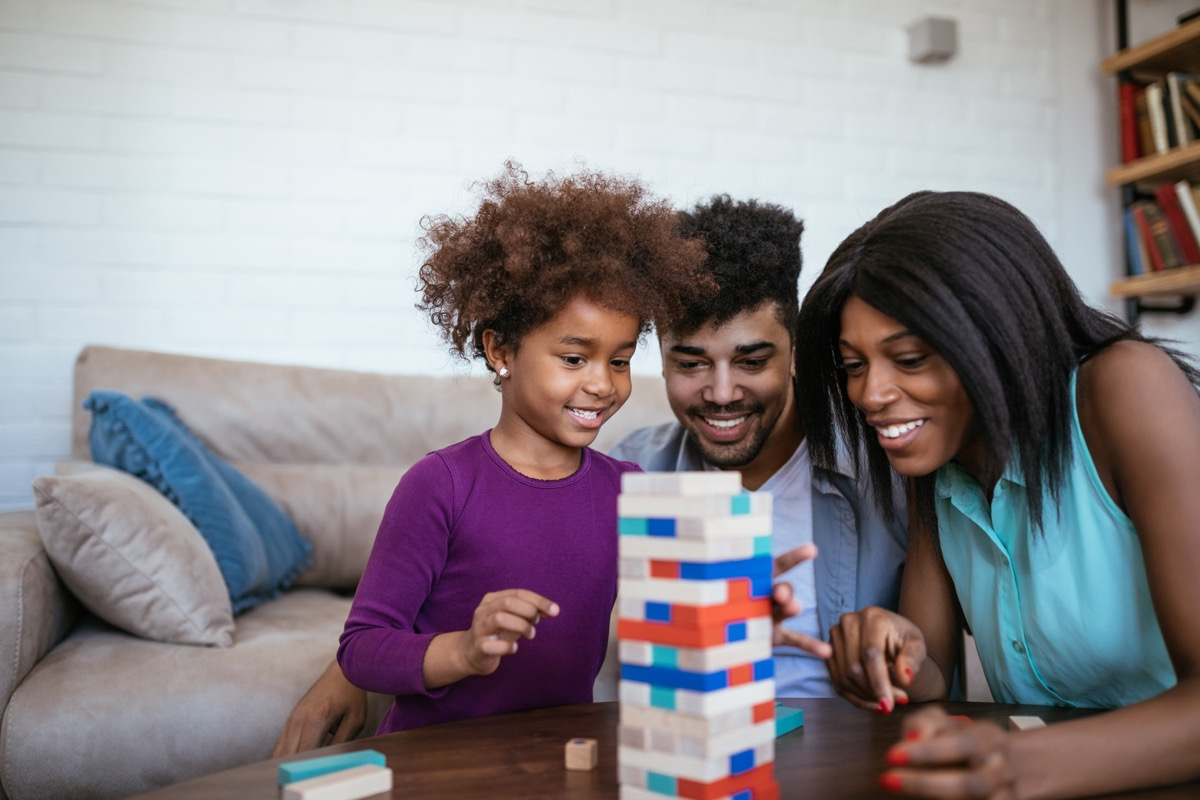 Black mother and father and young daughter play Jenga-like game