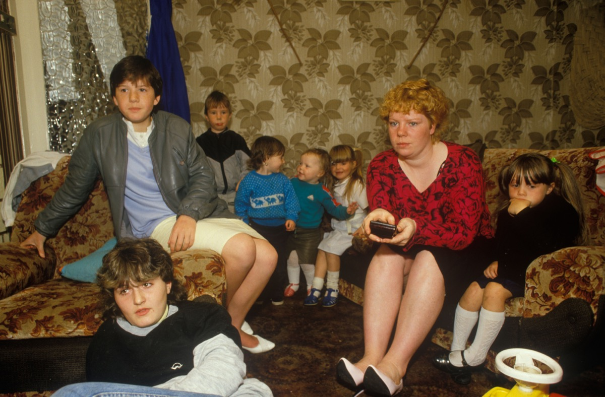 Single parent family. Mother and her seven children watching TV at home. Council estate Circa 1985