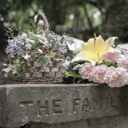 """Flowers on grave that reads """"The Family,"""" story of widow at 40"""