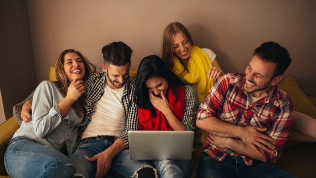Friends looking at laptop and laughing